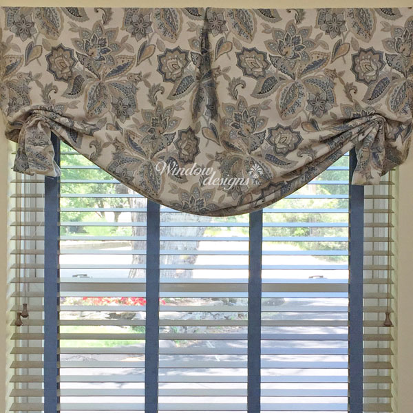 Center pleat butterfly Roman shade over a white alternative wood blind with decorative tape in a Shrewsbury, MA private office.
